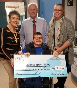 Oisin McGinty and his mother present a cheque to Kay Duffy and Seamus Cunningham