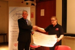 Margaret McAllister presents a cheque for £1,100 from Belvoir Players.